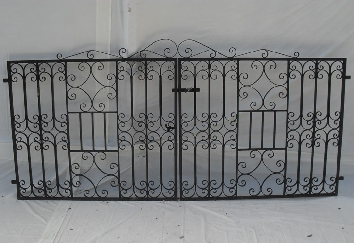 Pair of driveway gates which have been heavily decorated with hand forged scrolls